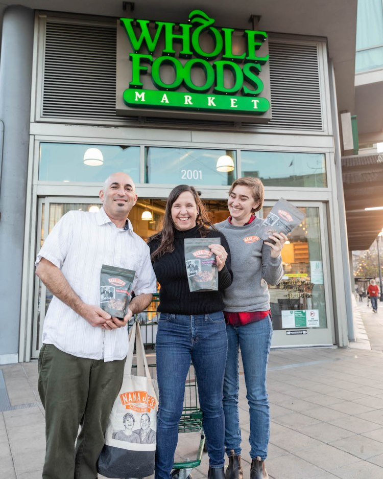 The Nana Joe's team (Joe, Michelle, and Natalie) standing in front of a Whole Foods sign holding up bags of their granola with smiles on their faces.