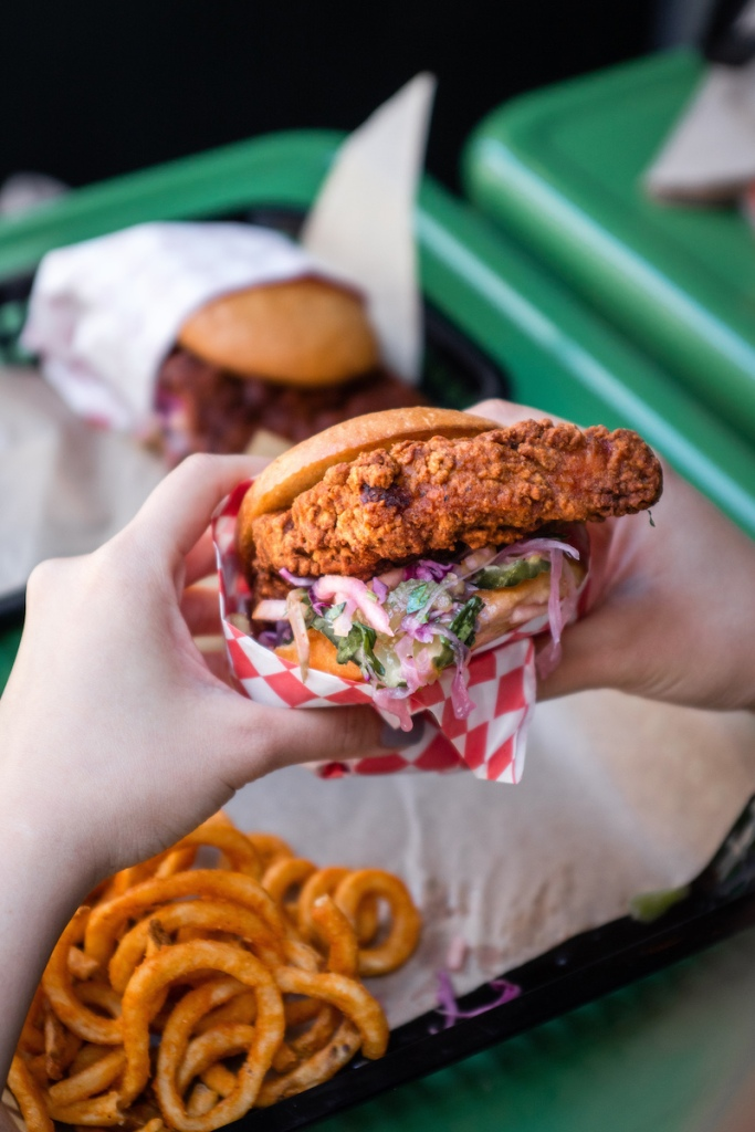 A close up of someone holding a deep fried chicken sandwich with a basket of curly fries on the table.