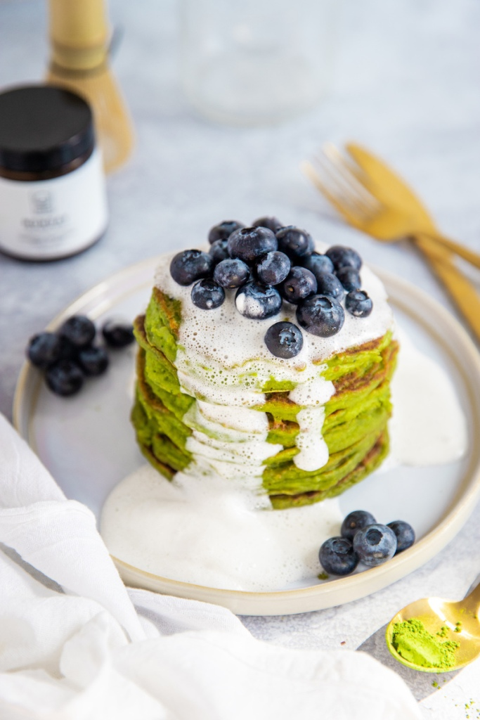 Matcha pancakes topped with dairy-free whipped cream.