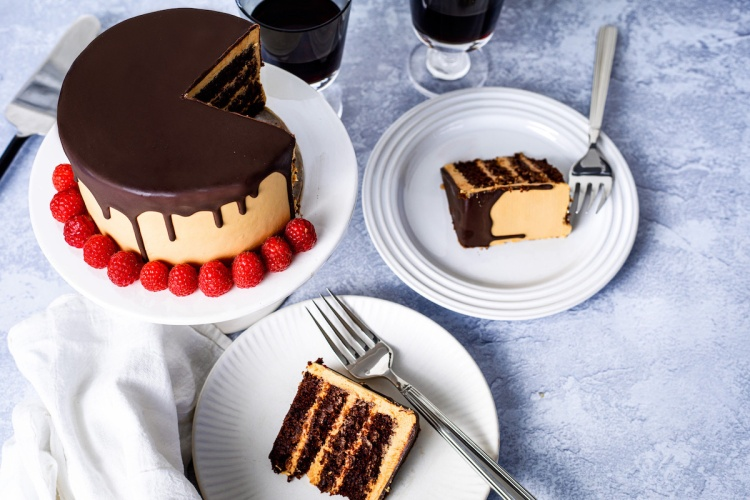 Chocolate peanut butter cake cut into slices served on plates.