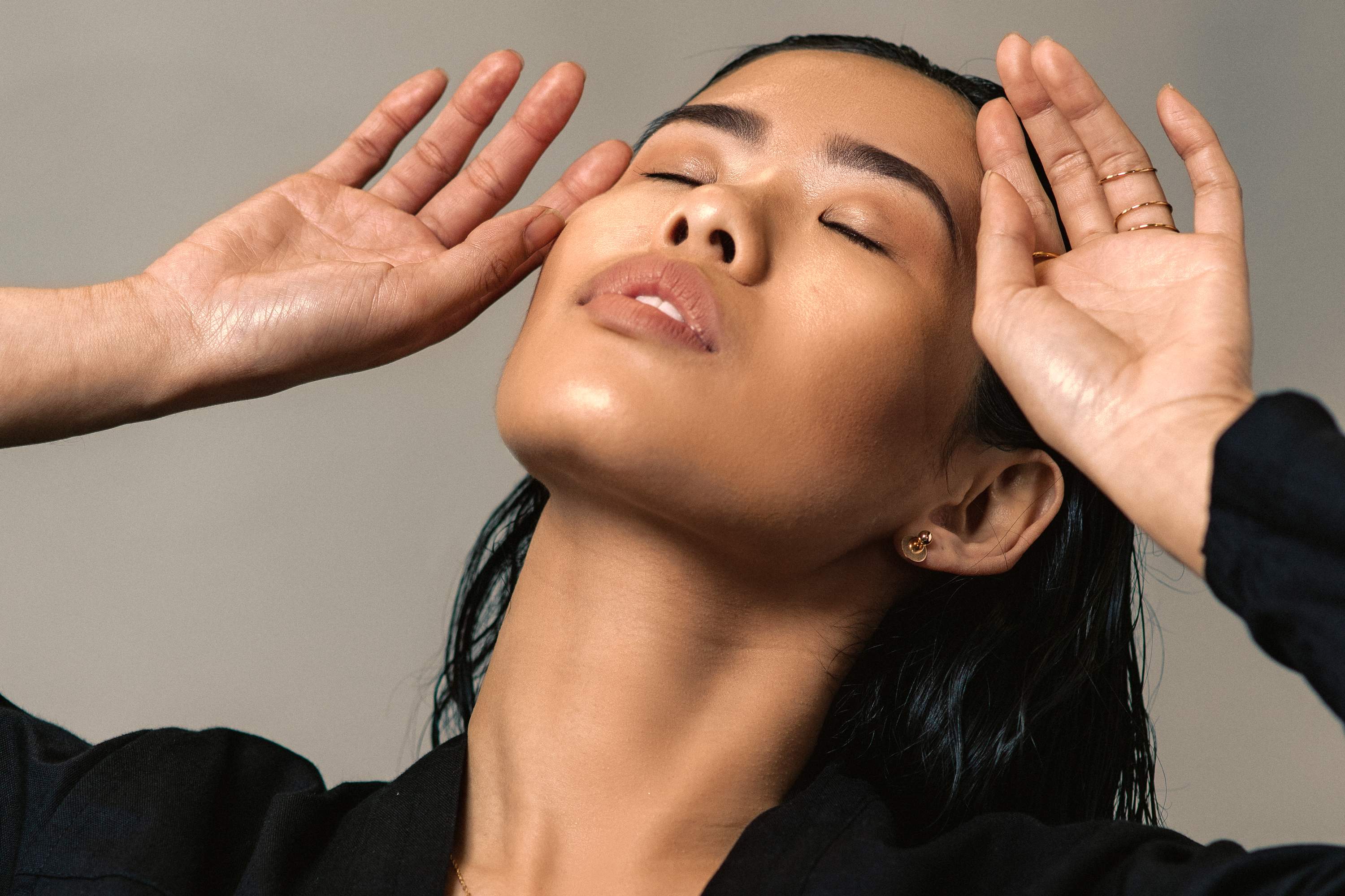 An Asian model with her eyes closed and both hands to her face.