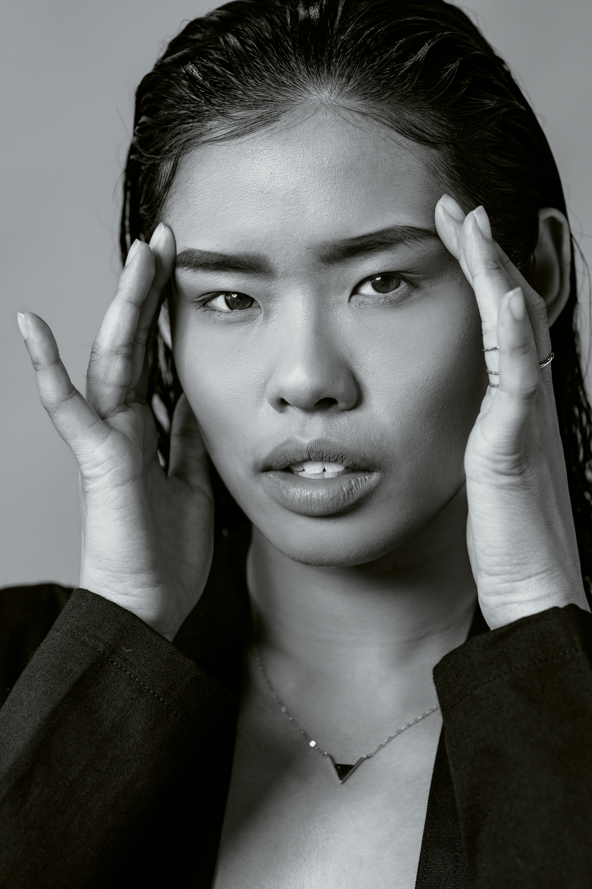 An Asian model with her hands up to her face.