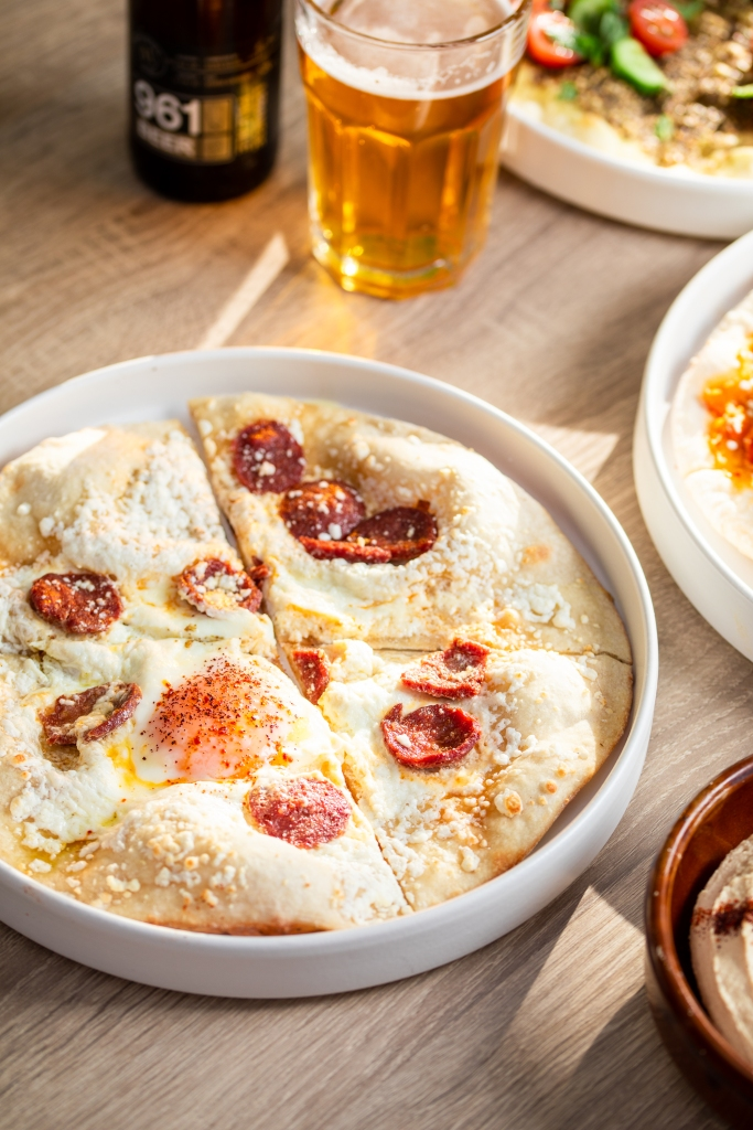 An Arab bread called mana'eesh with cheese, pepperoni, and an egg on top.