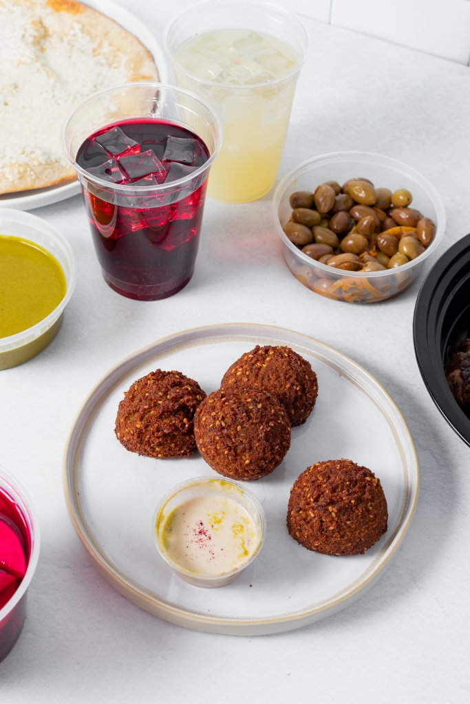 A plate of falafels with a tahini dip surrounded by other takeout containers from Reem's California.