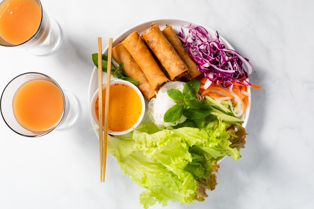 A plate of Vietnamese egg rolls with vegetables such as lettuce, pickled daikon and carrots, and sliced red cabbage.