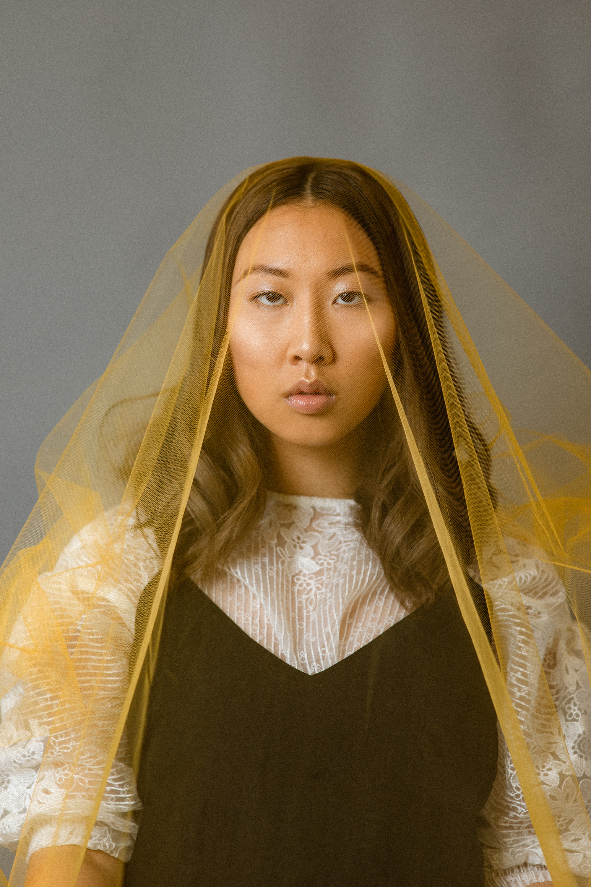 An Asian woman model is staring directly at the camera with yellow tulle covering her whole body.