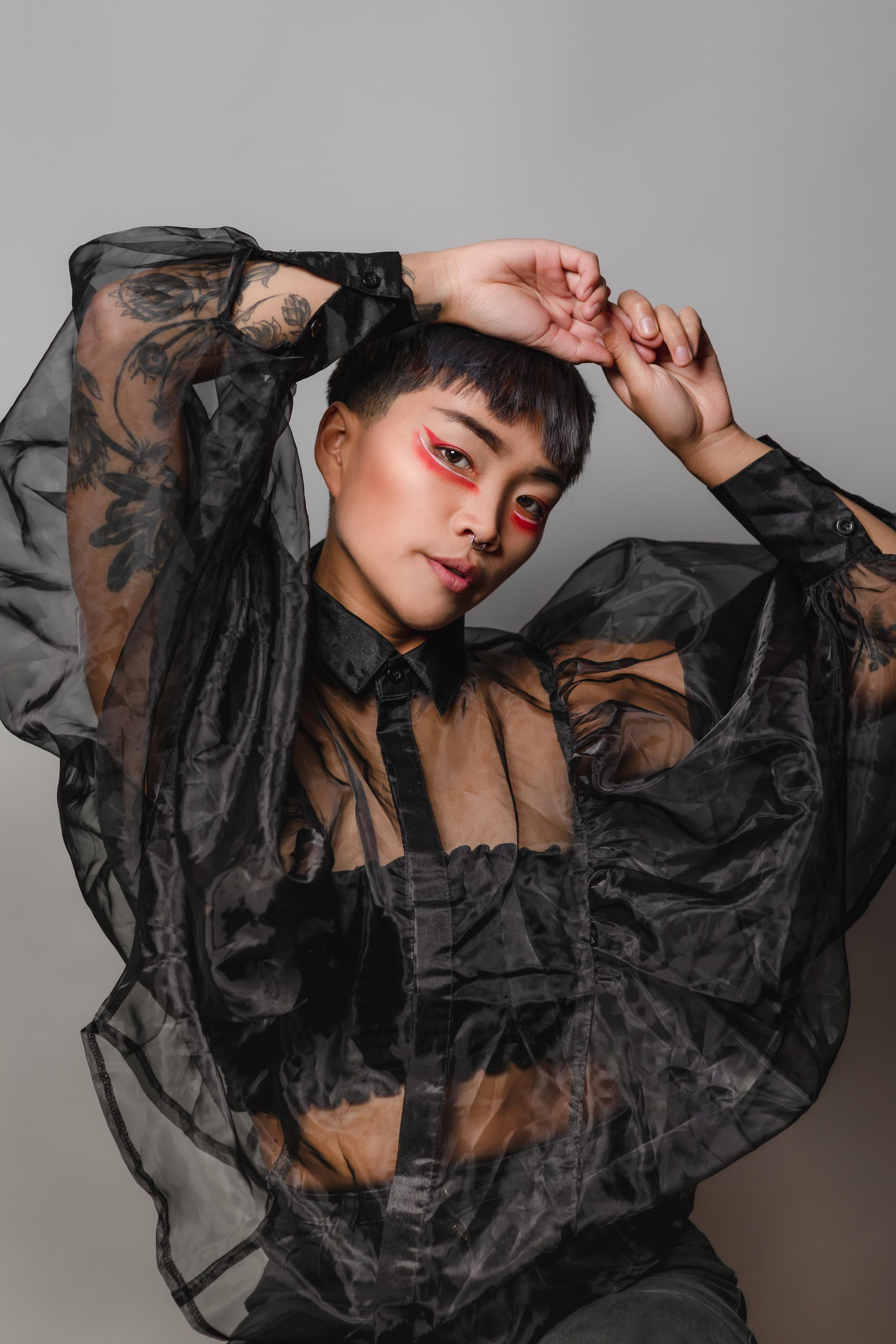 A Vietnamese gender-nonconforming model is wearing a tulle black shirt with their hands above their head.