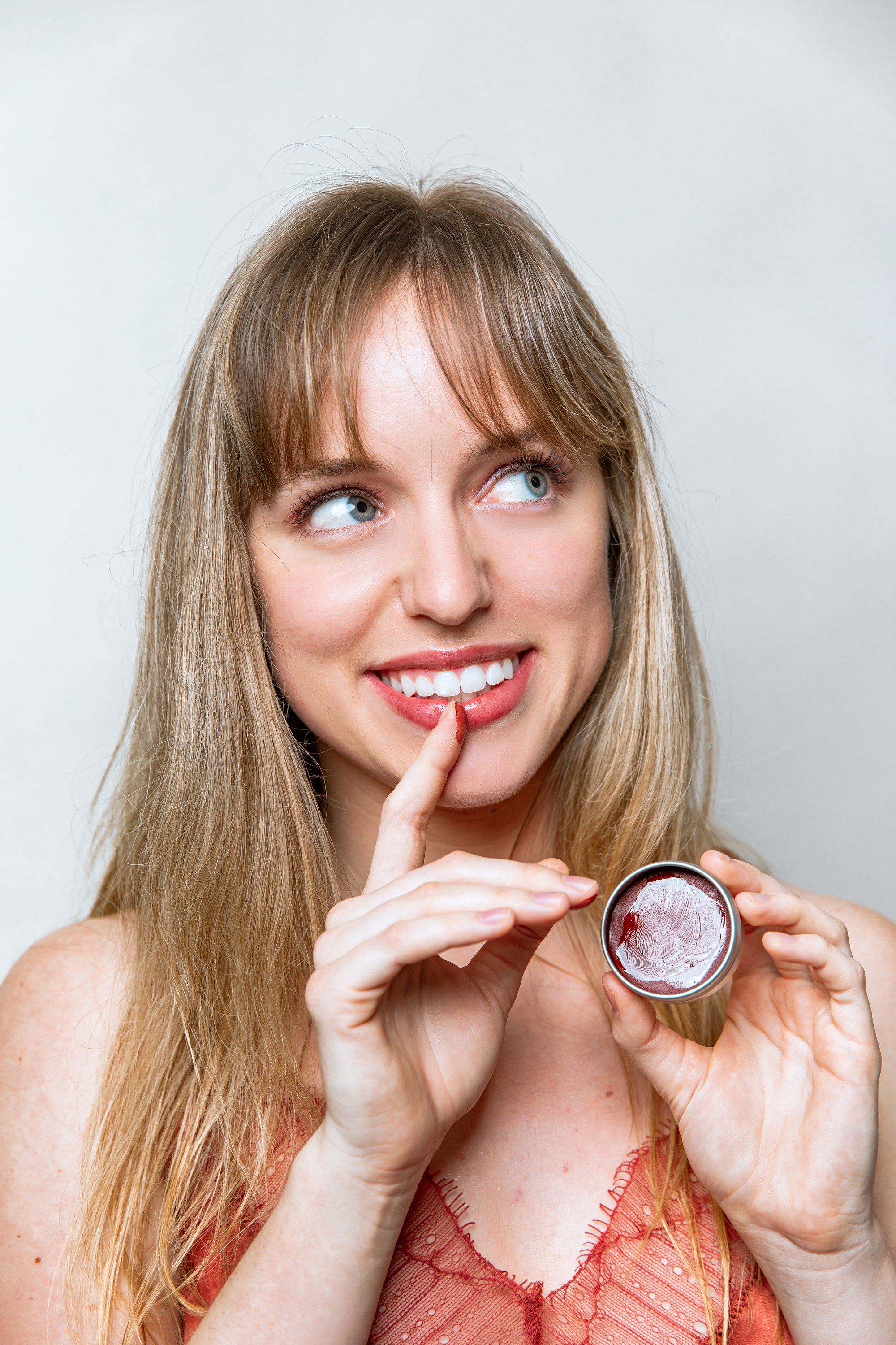 A woman smiling looking away while putting her finger with lip balm on her lip.