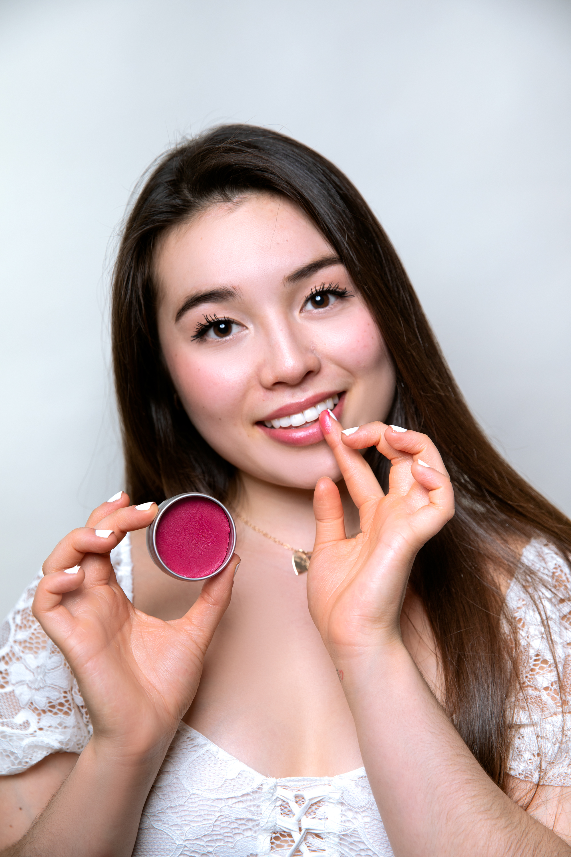 A woman putting on a plastic-free packaging lip balm onto her lips.