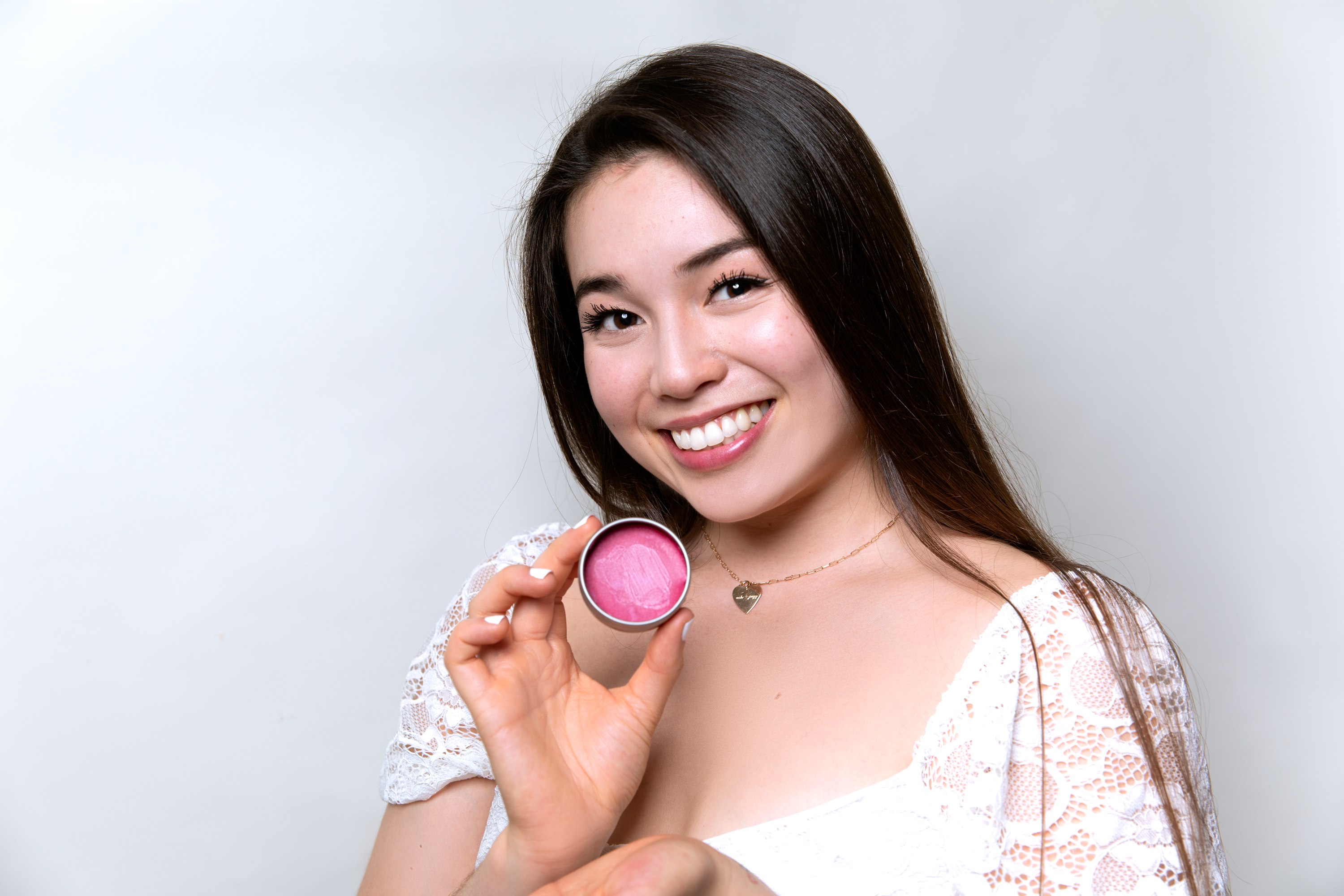 A woman smiling and showcasing a plastic-free packaged lip balm.