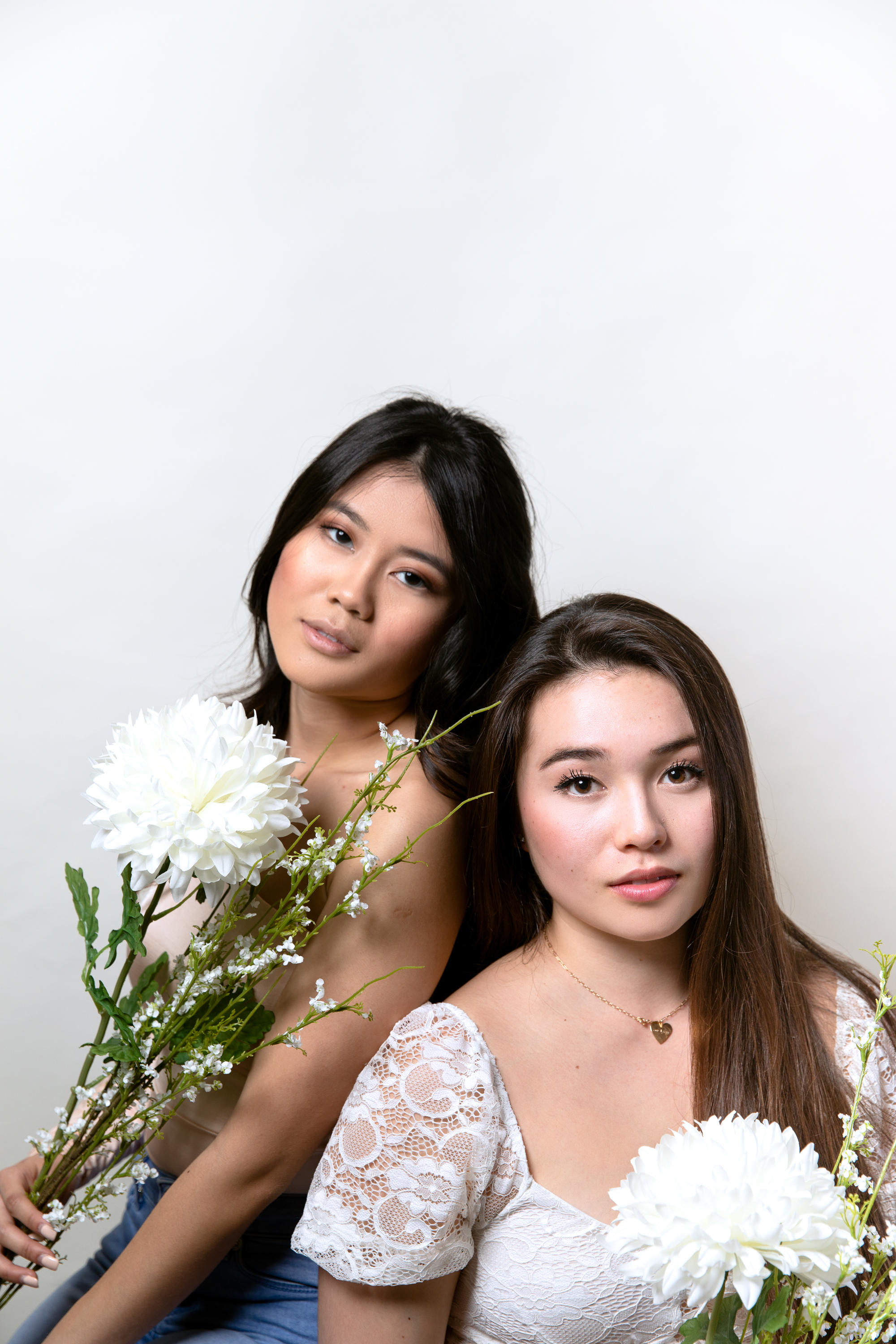 Two women solemnly looking at the camera holding white flowers.